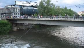 River surfing in Graz on the river Mur at the Hauptbrücke (main bridge).